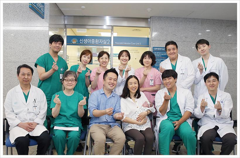 서울아산병원 어린이병원 신생아팀이 사랑이의 퇴원을 축하하고 있는 모습
