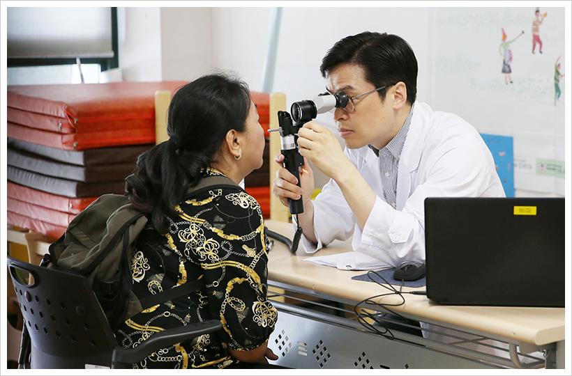 이날 무료진료 활동에 참여한 이주용 서울아산병원 안과 교수가 진료소를 찾은 외국인 근로자의 눈을 살펴보며 진료하고 있다.